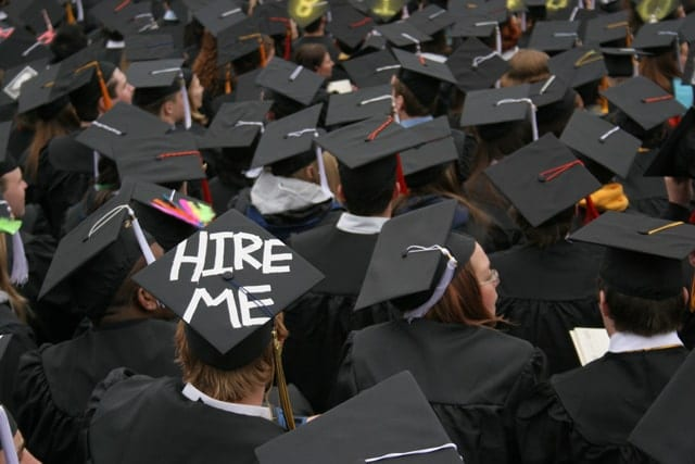 Graduate caps with one saying hire me