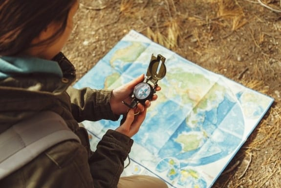 Person using compass and map to navigate