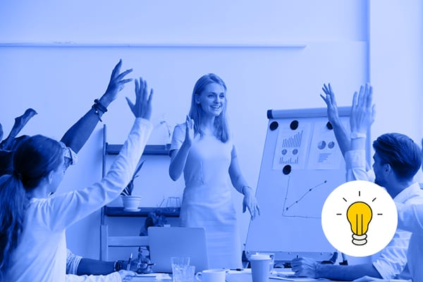Using digital tools to improve your candidate experience article image. A young woman stands in front of a whiteboard. People with raised hands sit around her